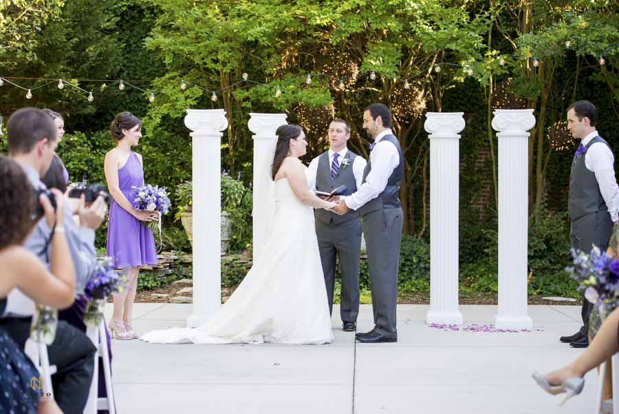 the bride and groom holding hands during their wedding ceremony at The Garden on Millbrook