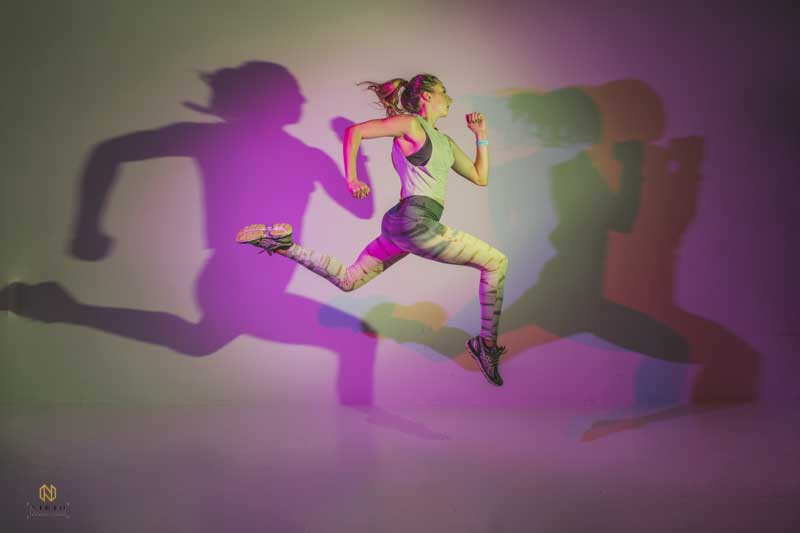 woman jumping in the air with her shadows behind her in different colors