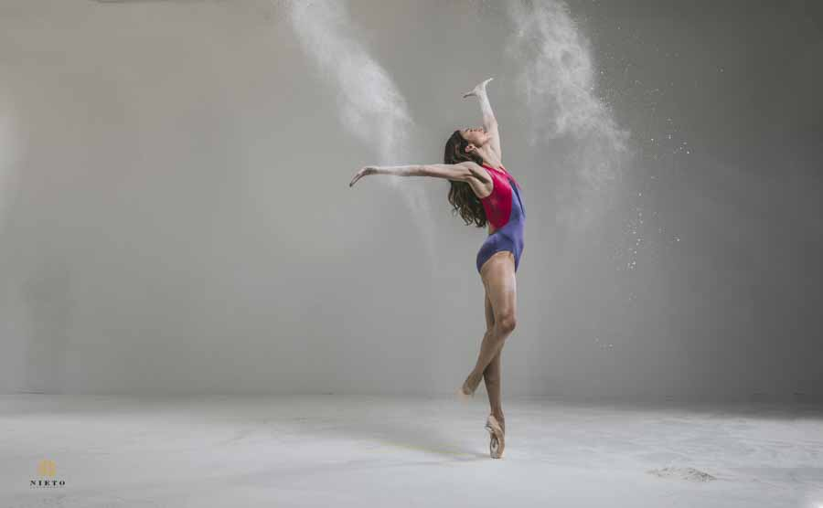 ballet dancer throwing flour in the air for her portrait