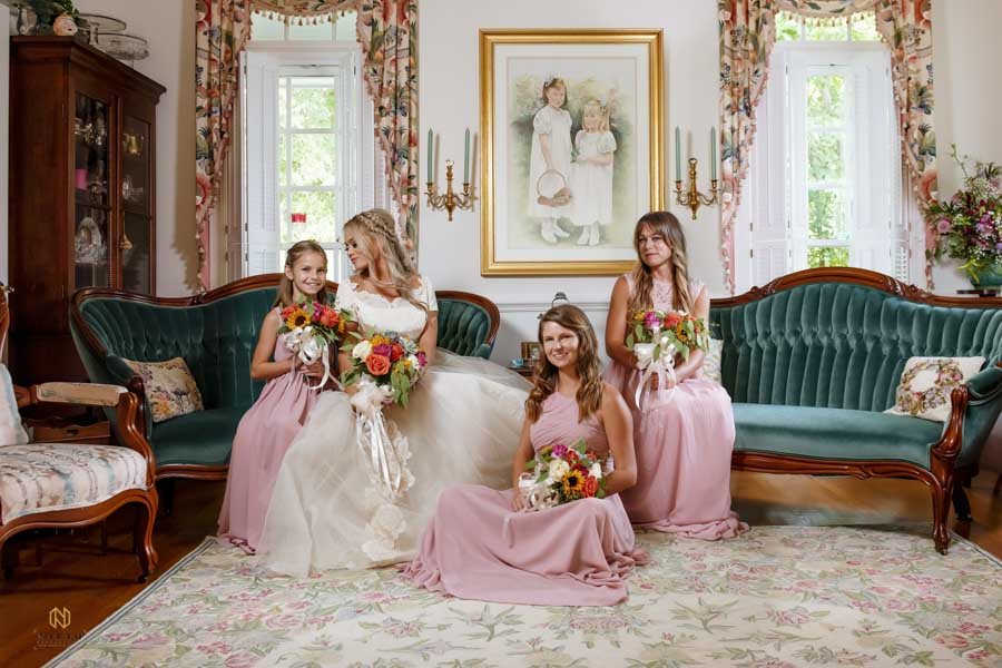 Bride looking at her junior bridesmaid as they pose with the other maids for a portrait in the parlor room
