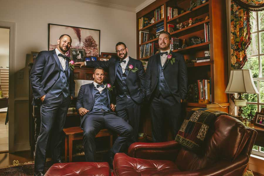 Group portrait shot in doors a groom sitting with his groomsmen standing around him