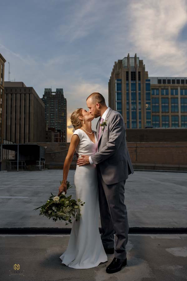 Bride and Groom kissing in a parking deck at sunset during their Stockroom wedding