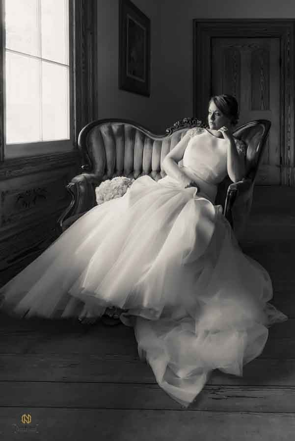 black and white bridal portrait of bride sitting in an antique chair