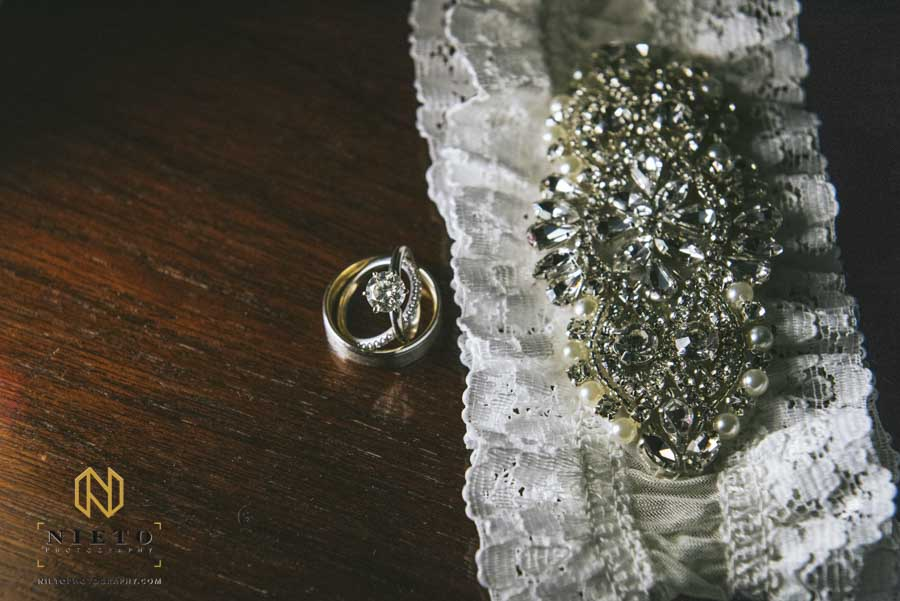 detail image of the rings and brides garter on a wooden table top
