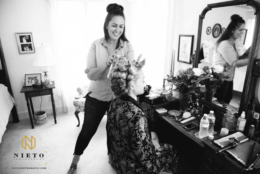 black and white image of the hairstylist working on the brides hair