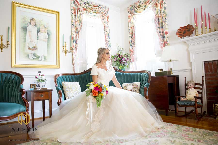bridal sitting on her parents couch posing for a portrait with her bouquet in hand