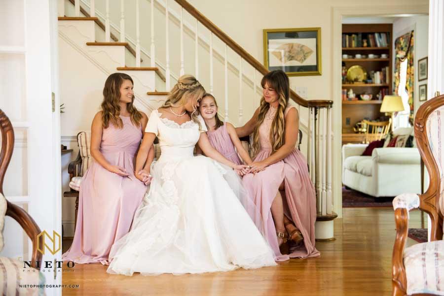 a bridal portrait with all the bridesmaids and bride sitting beside each other