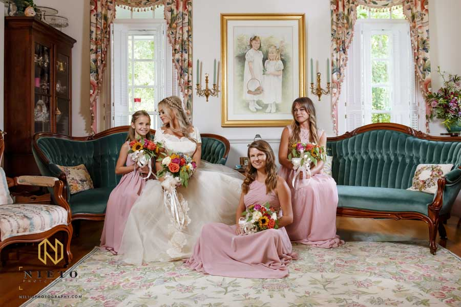 bridesmaids and bride posing for a formal portrait in the family living room