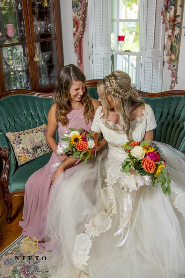 bride and her matron of honor sitting in a parlor chair laughing together