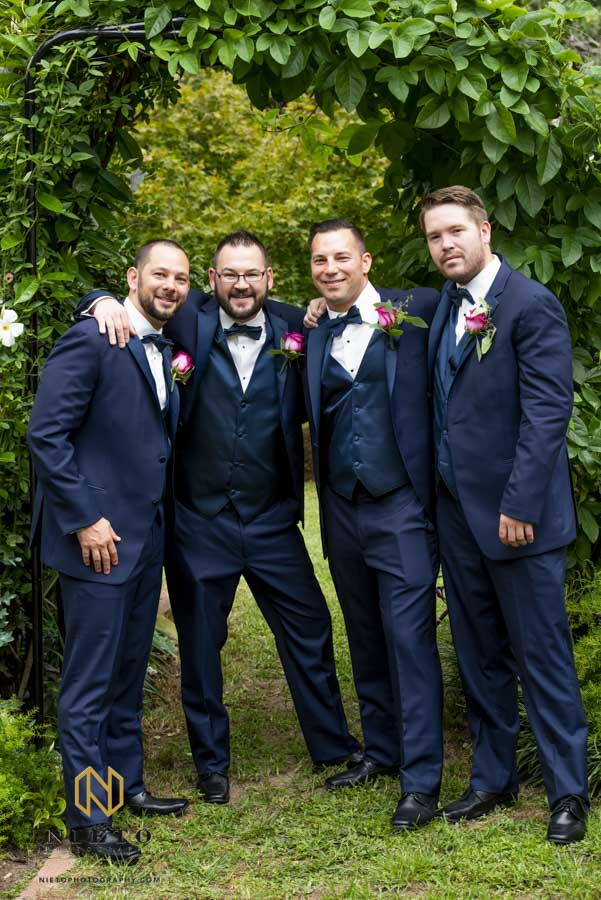 groom and his groomsmen posing for a portrait with their arms around each other