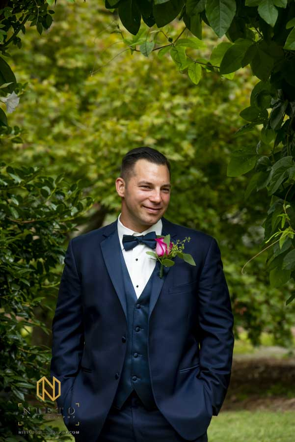 groom smiling as he poses for a solo portrait before his backyard wedding ceremony