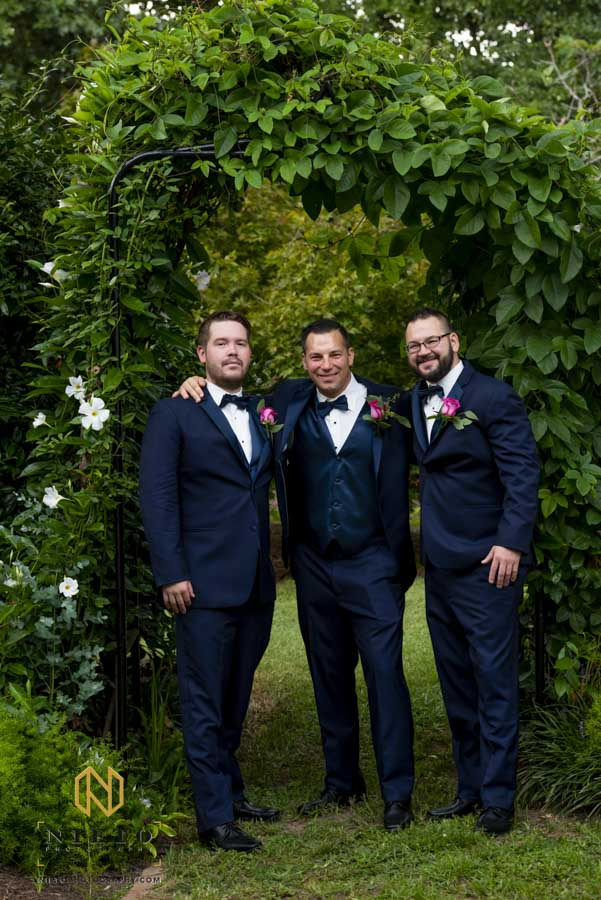 groom and his brothers posing for a portrait under the arbor for his backyard garden wedding