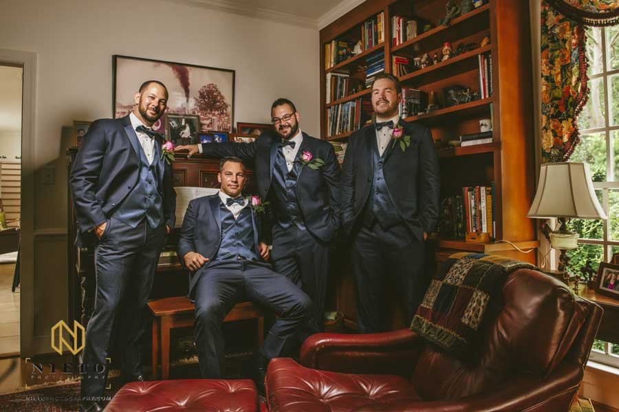 groom and groomsmen posing for a portrait in front of a piano