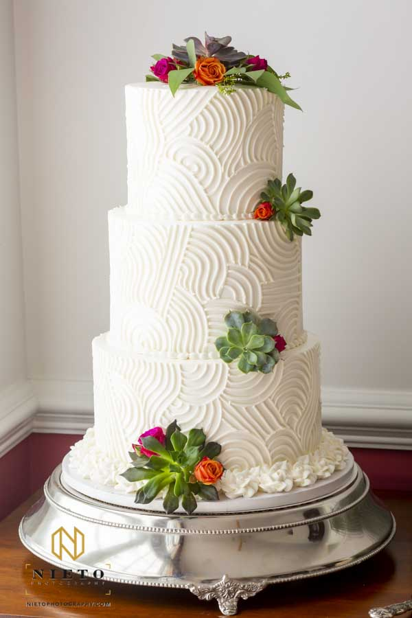 cake decorated by succulents and small flowers