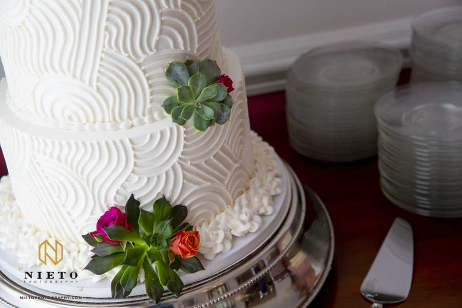 close up of a white cake decorated with succulents and small flowers