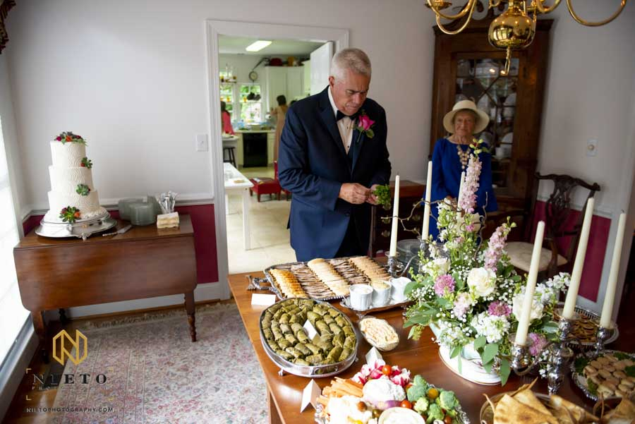 father of the groom placing out appetizers before the wedding ceremony