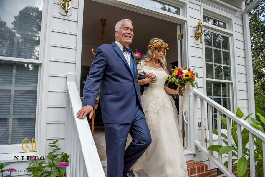 father of the bride leading his daughter down stairs to her backyard garden wedding
