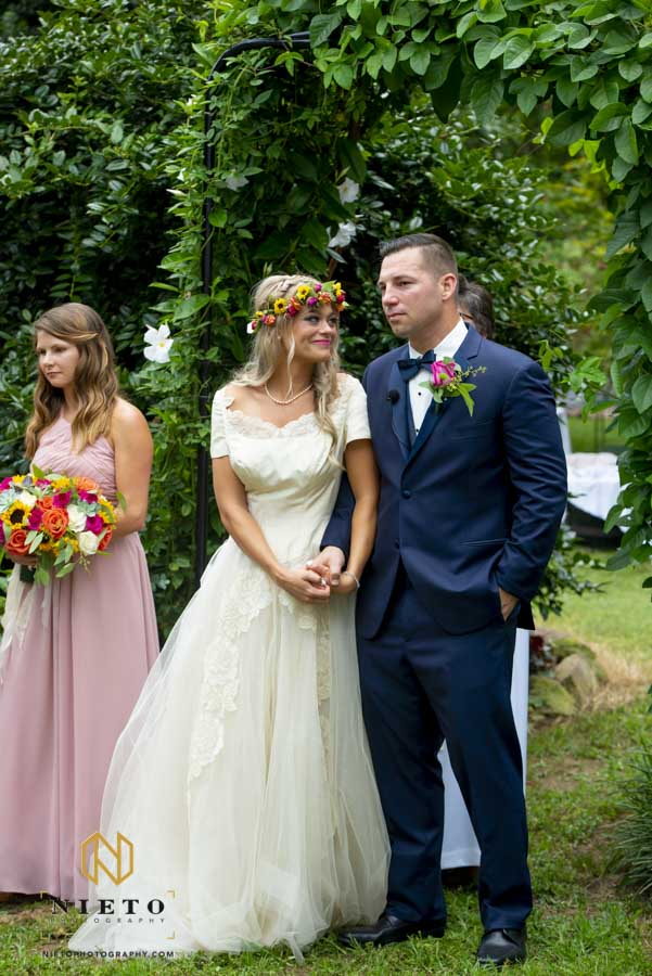 bride smiling at groom as they listen to the soloist