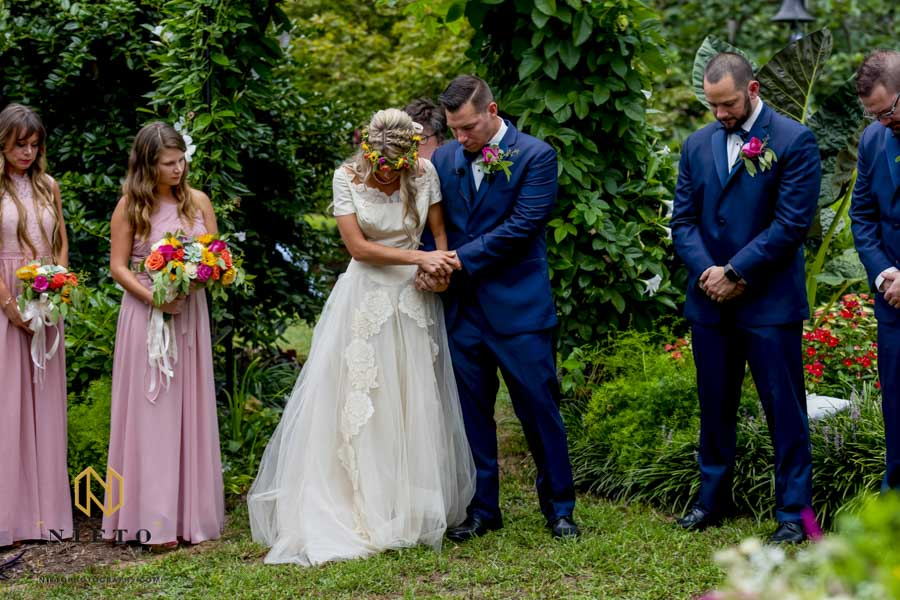 bride and groom golding hands and bowing their heads during the prayer