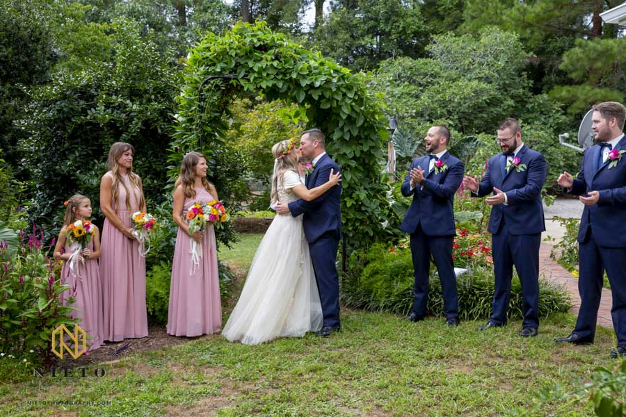 bride and groom kissing at the end of their ceremony with the wedding party smiling and clapping