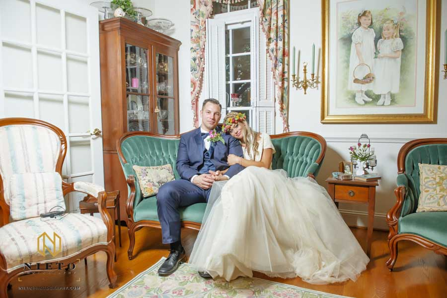 groom and bride sitting in the parlor of her parents house posing for a portrait as it rains outside