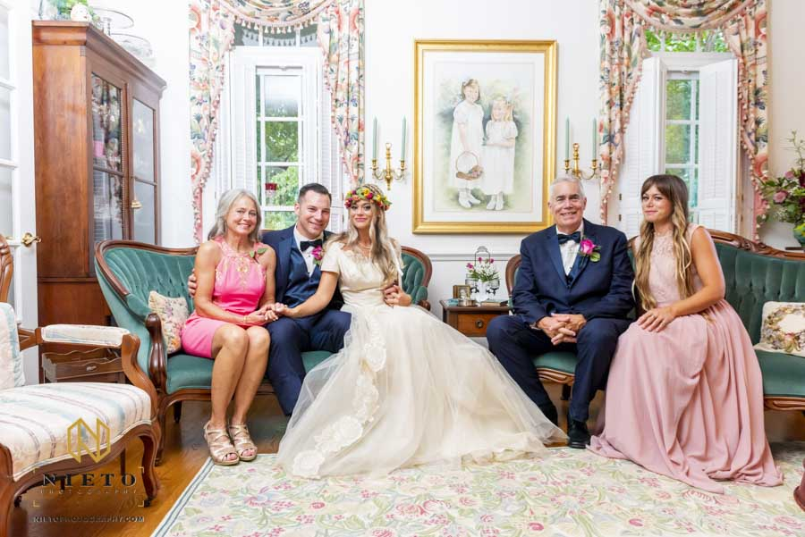 formal family portrait in the family living room of bride and groom and the brides family