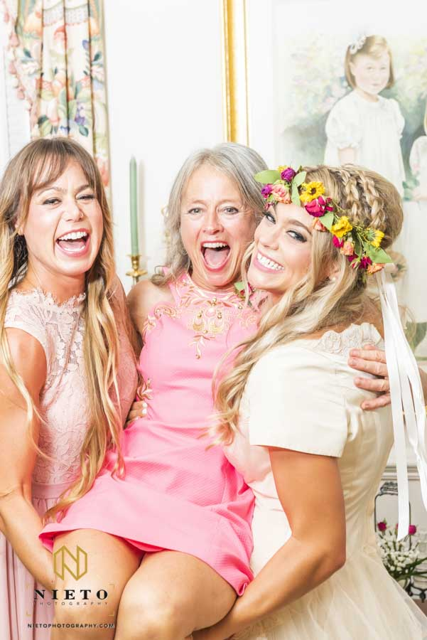 mother of the bride and her daughters picking her up and laughing