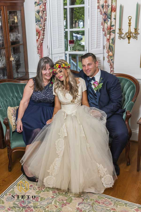 mother of the groom and bride and groom posing for a portrait