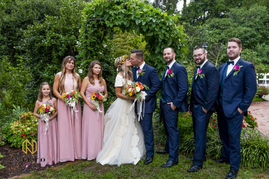 bridal party portrait with groom and bride kissing