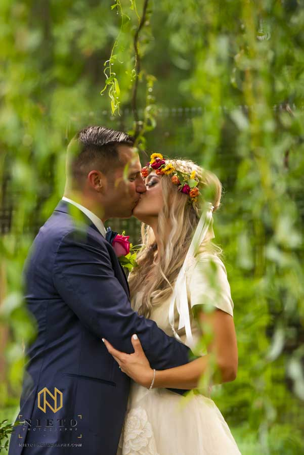 bride and groom kissing under a willow tree