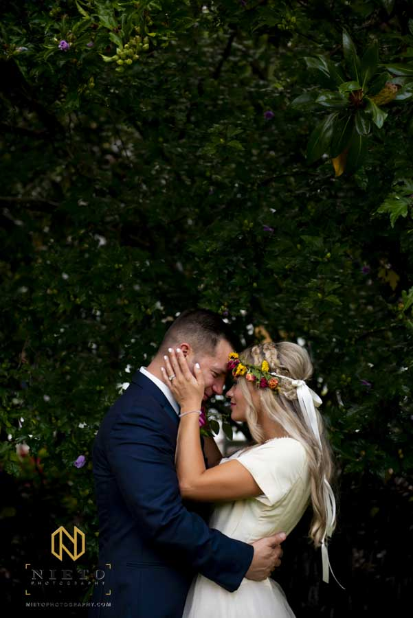 bride and groom touching foreheads as the bride holds the grooms hand with both her hands