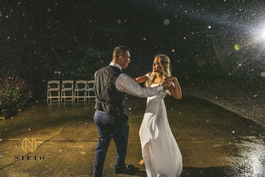bride and groom dancing in the rain together