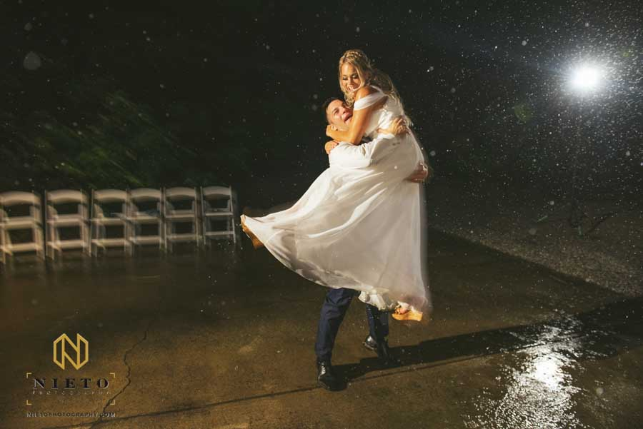 bride and groom dancing in the rain together as the groom pics her up
