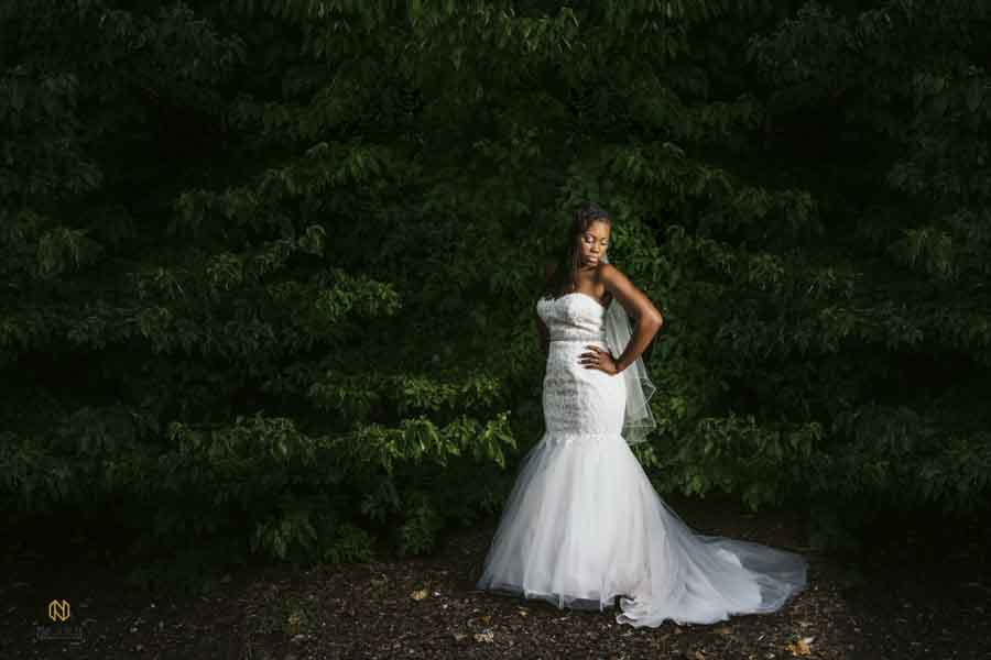 full body bridal portrait against green leaf back drop at Chapel in The Woods in Louisburg NC