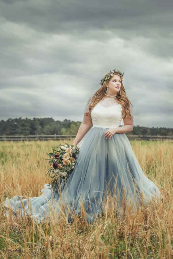 Bride in a blue and white dress posing in a filed of broom straw with dark sky behind her