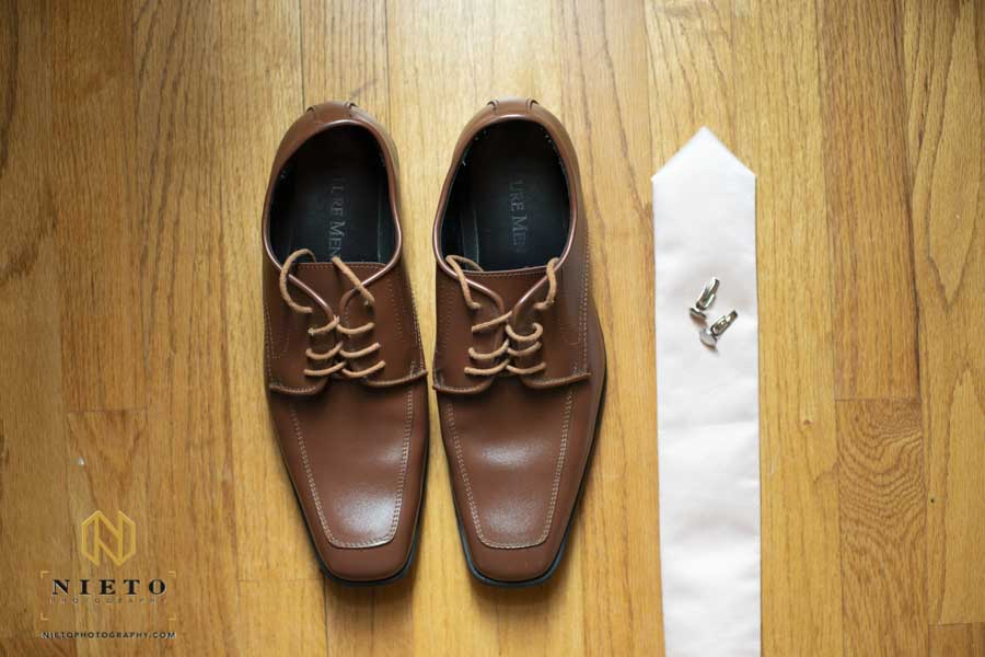 grooms shoes, tie, and cuff links spread out on the floor for a detail shot
