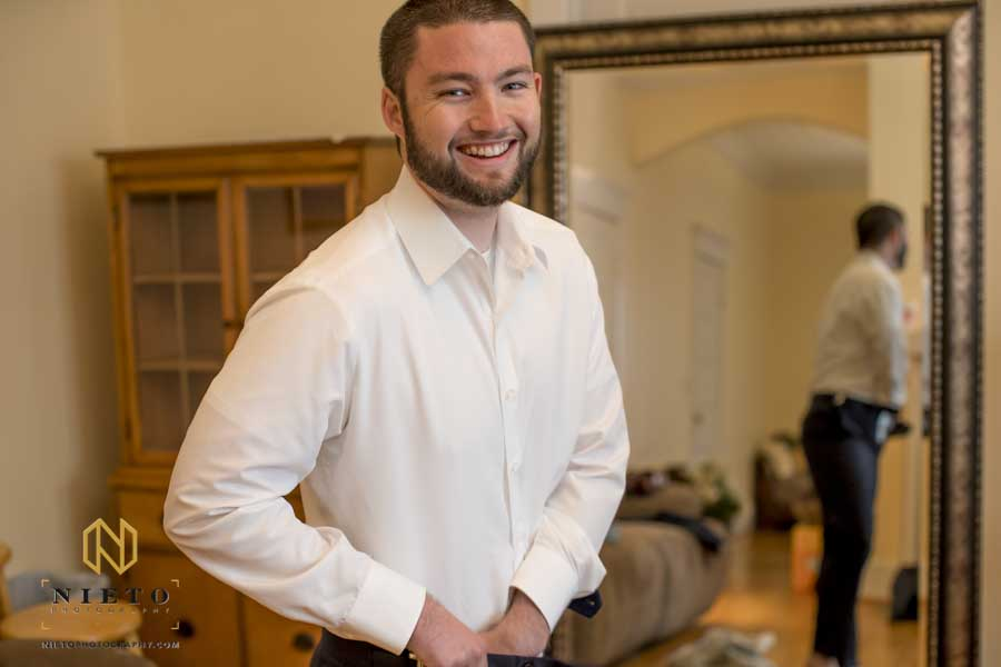 groom laughing while he is getting dressed