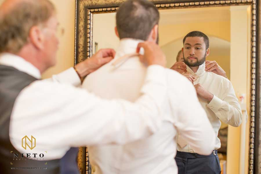 groom having his collar and tie adjusted by his father as they look in a mirror