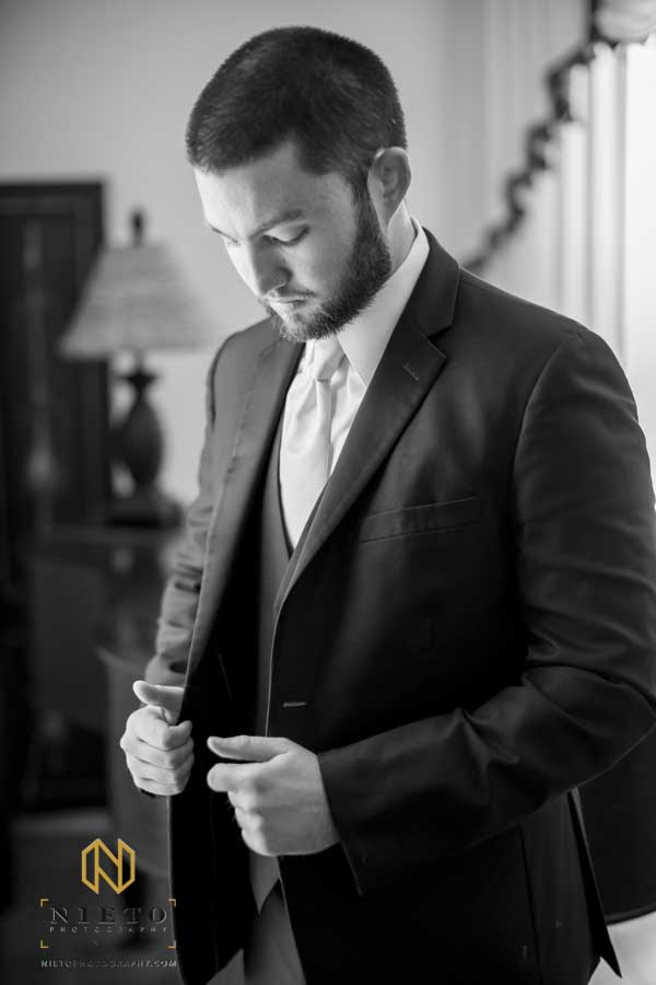 black and white image of the groom adjusting his jacket
