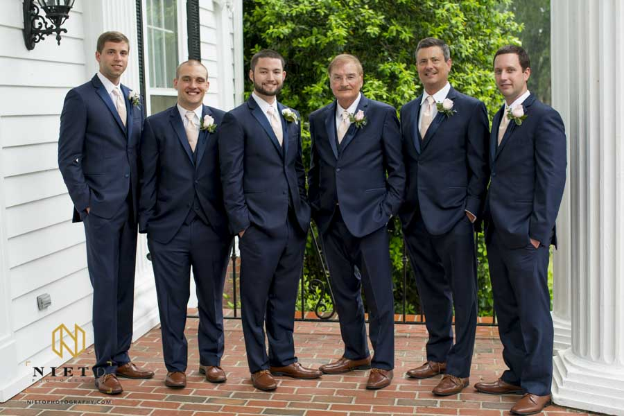 formal portrait of the groom and groomsmen on the front porch of the Hudson Manor