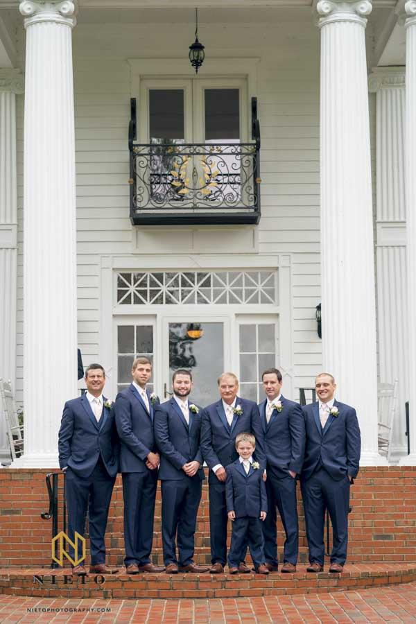 formal portrait of groom and his groomsmen in front of the Hudson Manor