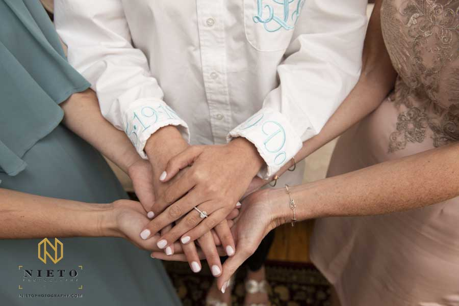 three generations of hands holding each other with the brides hand on top grandmother, mother, daughter
