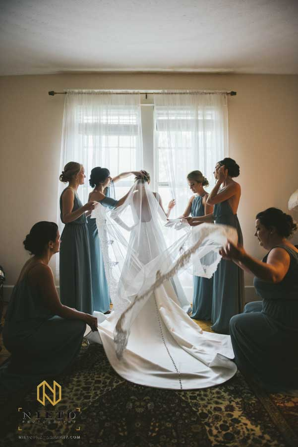 bridesmaids arranging the brides dress and veil inside the Hudson Manor