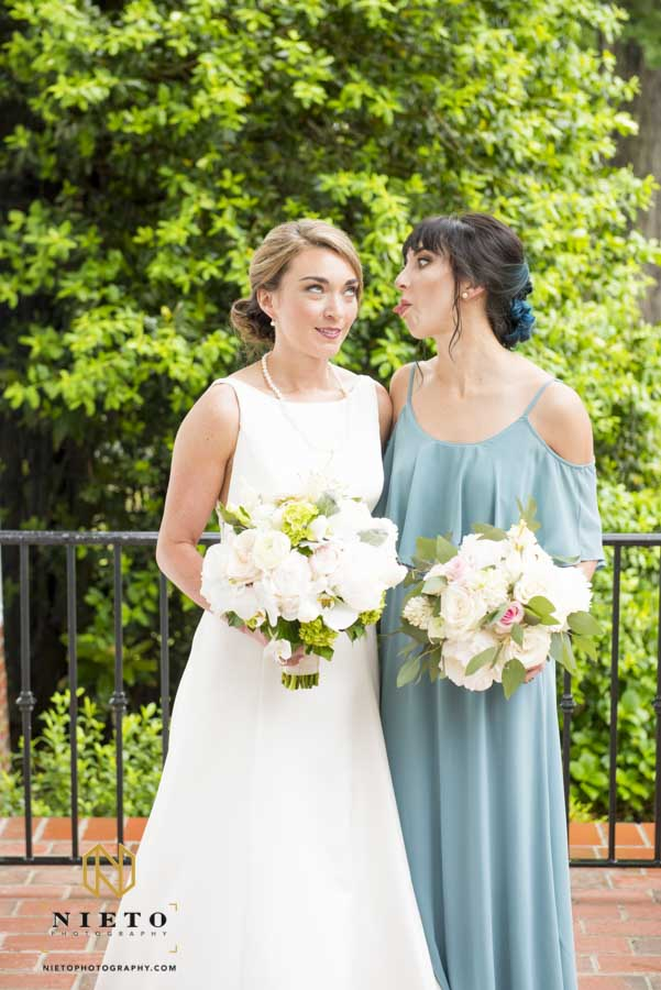 bride rolling her eyes while here sister sticks out her tongue at her