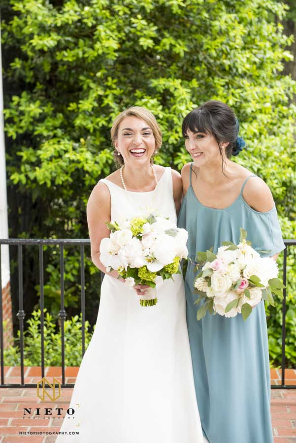bride and sister laughing together while they pose for a portrait