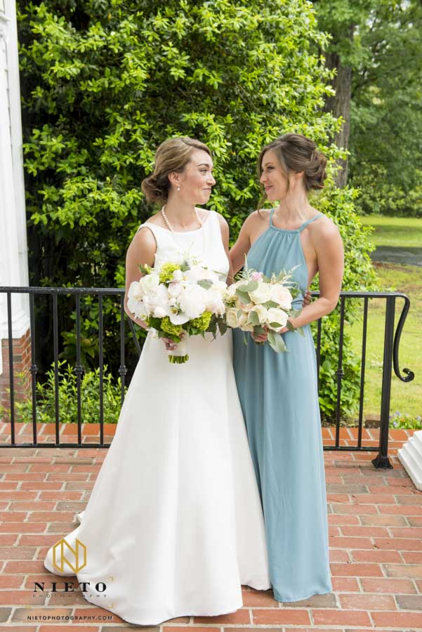 bride and bridesmaid smile at each other