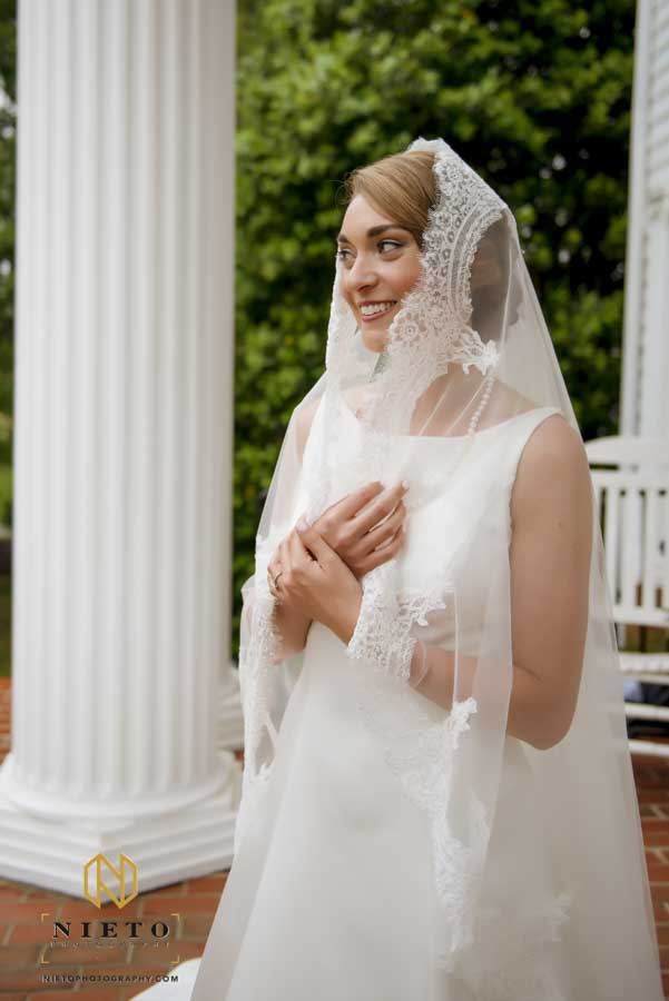 bride with her veil around her face as she smiles