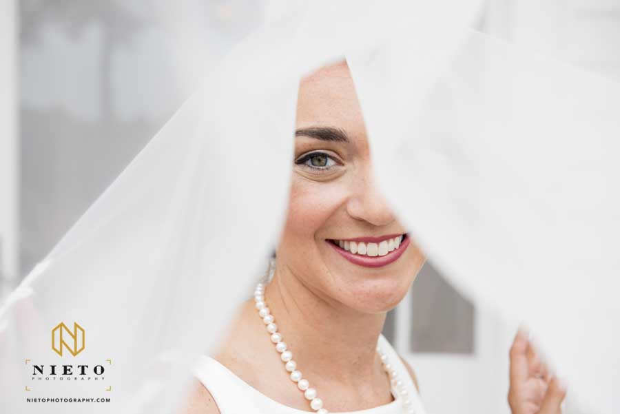 bride smiling with just one eye showing as her veil covers her face