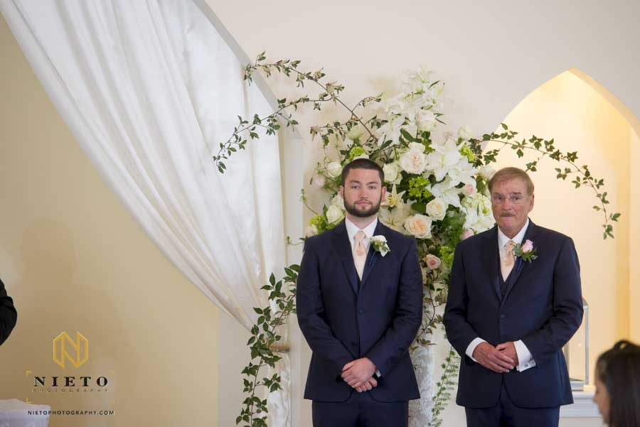 groom and best man standing at the front of the aisle before the ceremony starts