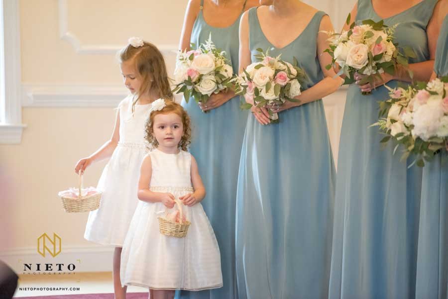 flower girl smiling as she stands in front of the bridesmaids